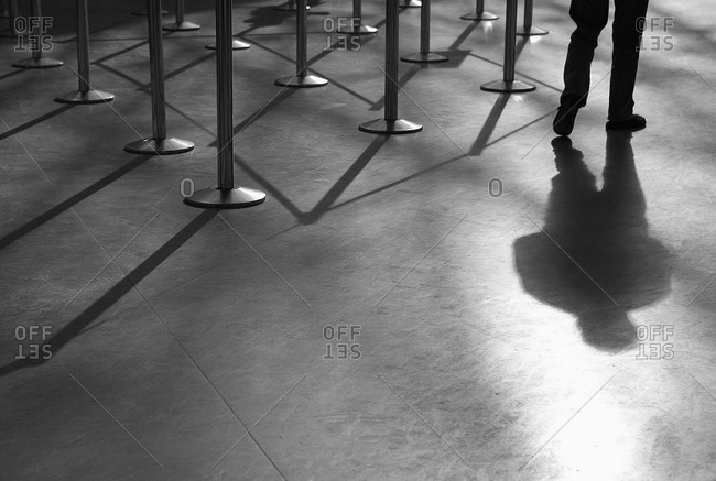 Shadow of man and roped-off barriers