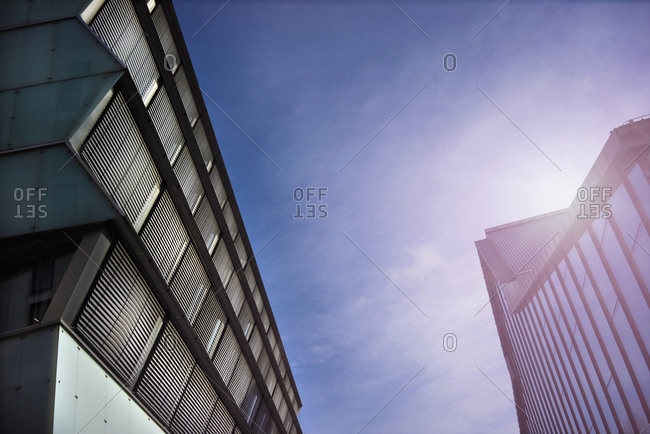 Low angle view of sunbeams over modern buildings