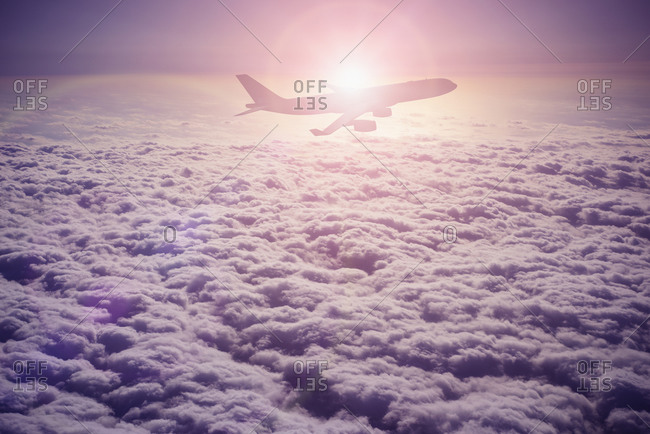 Silhouette of airplane flying over clouds