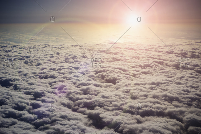 Sun shining in sky above clouds
