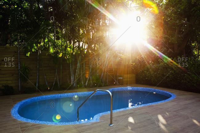 Sunbeams over swimming pool in backyard