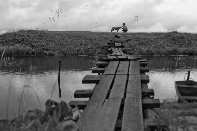 Girl petting dog near rustic wooden bridge crossing river
