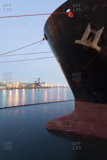 Close up of bow of ship docked in industrial harbor