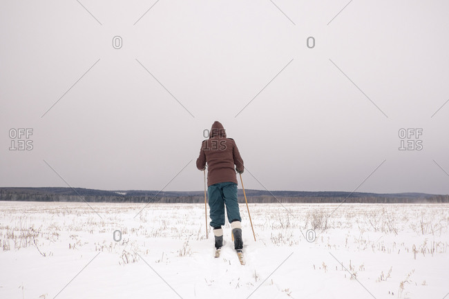 Woman cross-country skiing in snowy field