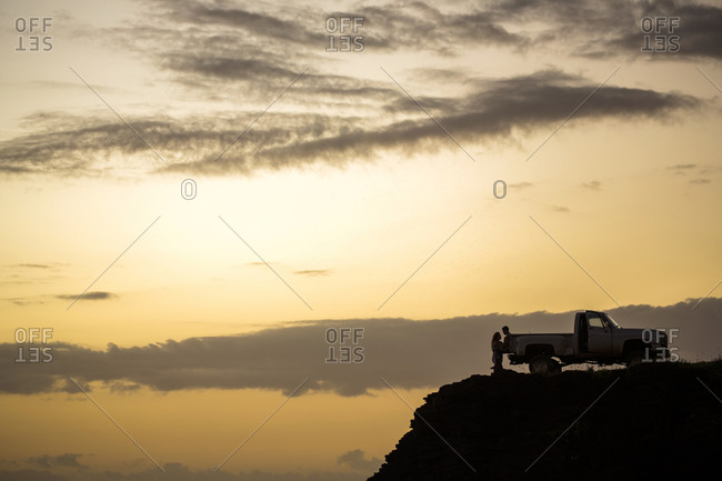Silhouette of people sitting on pickup truck on cliff at sunset