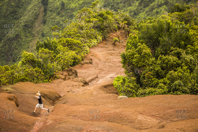 High angle view of boy jumping on remote mountainside