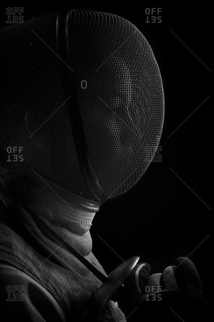 Profile of a woman in a fencing outfit stock photo - OFFSET