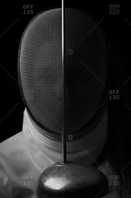 Portrait of a woman in a fencing mask with a sword