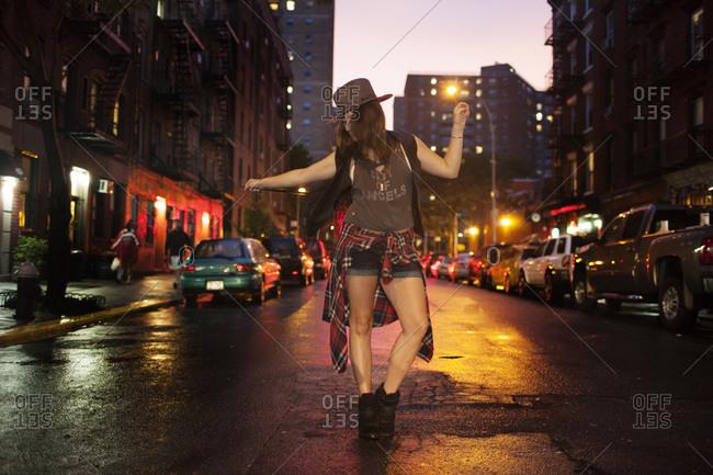 Trendy woman dancing in street
