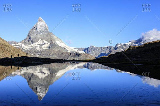 Hikers by Matterhorn reflected in lake, Switzerland
