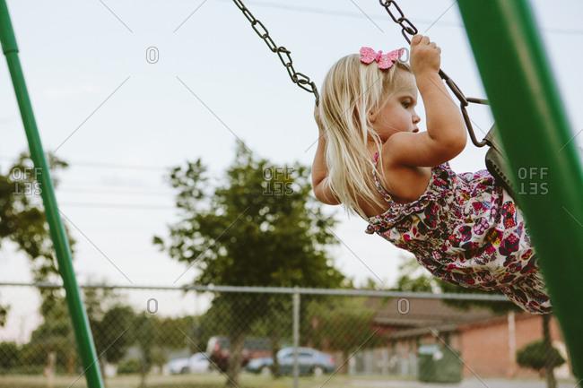 Little girl swinging on a park swing set