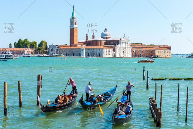 Venice, Italy - August 2, 2015: Tourists in gondolas in Venice canal in Venice, Italy