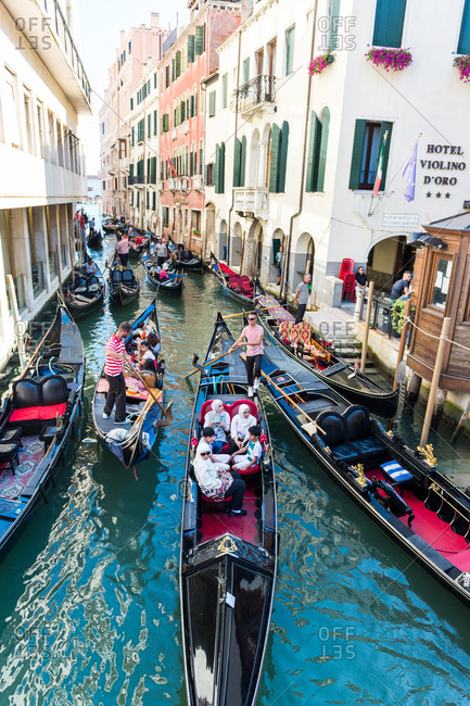 Venice, Italy - August 2, 2015: Venice canal filled with tourists in gondolas in Venice, Italy