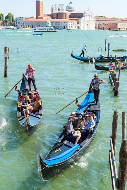 Venice, Italy - August 2, 2015: People taking tour in gondolas in Venice canal in Venice, Italy