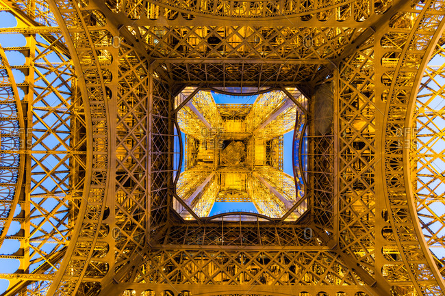 Underside of the Eiffel Tower glowing at twilight, Paris