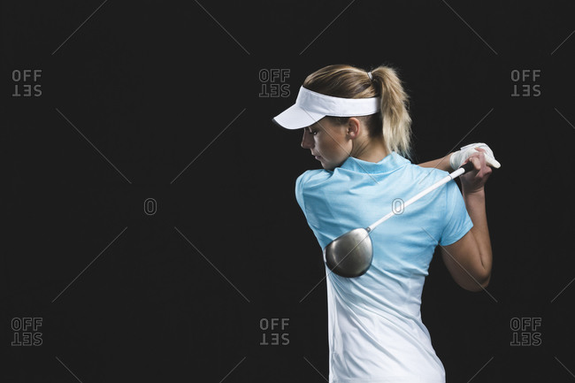 Blonde woman swinging a golf club