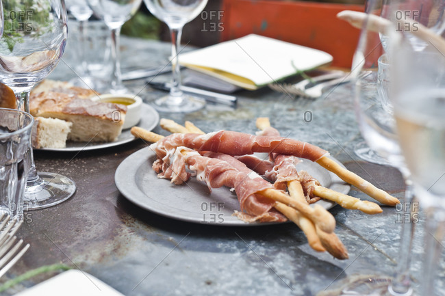 A starter of Italian prosciutto rolled on breadsticks at restaurant table