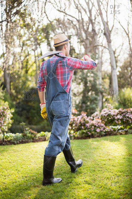 Gardener man walking with his shovel in the garden