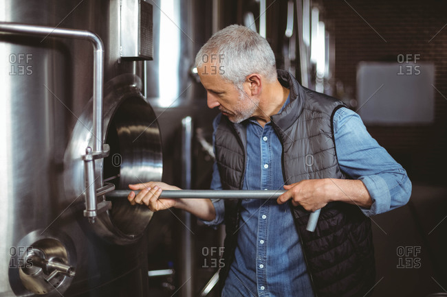 Brewer checking large vats at the local brewery