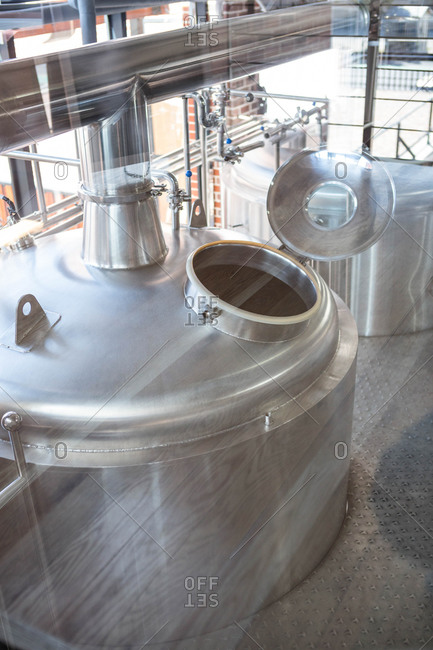Large vat of beer seen through glass at the local brewery