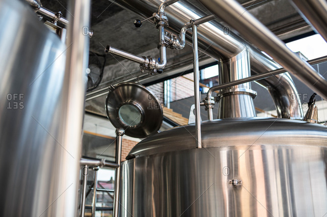 Large vat of beer with an open lid at the local brewery