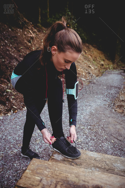 Fit brunette with armband tying her shoe lace in the woods