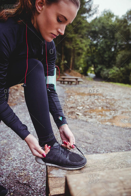 Close up of fit brunette with armband tying her shoe lace in the woods