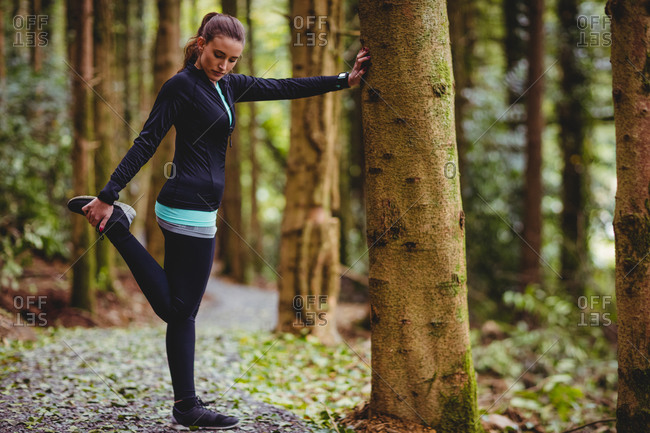 Fit woman looking down while stretching her leg against a tree in the woods