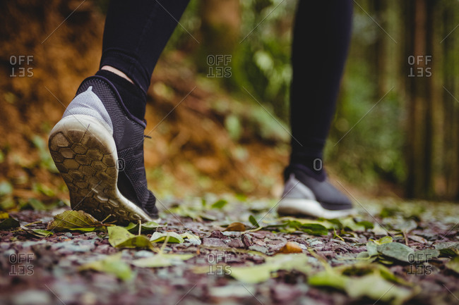 Close up view of woman sport shoes running in the woods