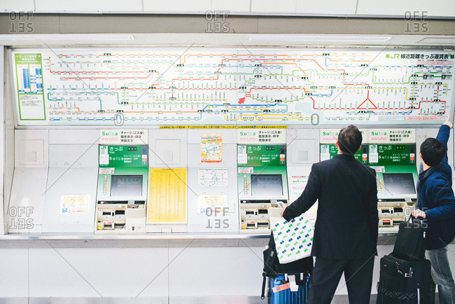 Two travelers attempt to decipher a railway map in Japanese train station