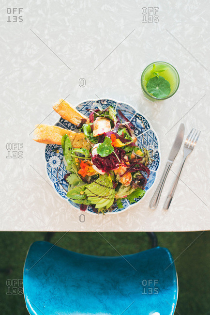 Overhead view of a colorful salad plate on table before a blue chair