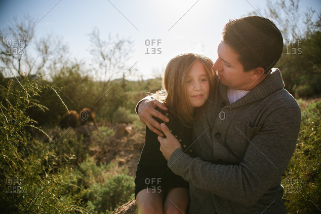 Dad giving girl hug in rural desert