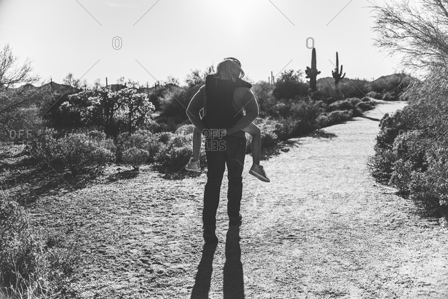 Dad giving girl piggyback ride in desert