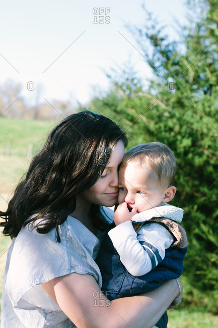 Woman holding and nuzzling her little boy