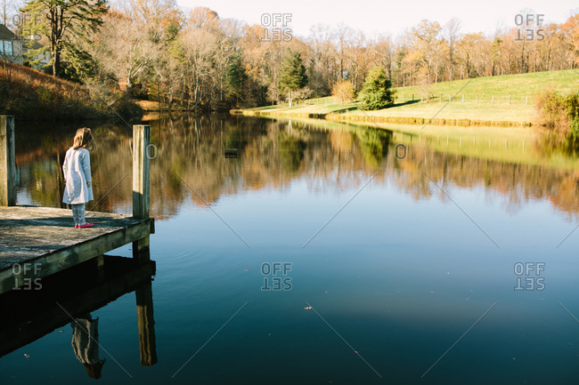 Girl standing on the end of a dock looking at a lake
