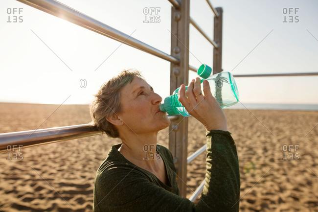 Woman hydrating on a beach