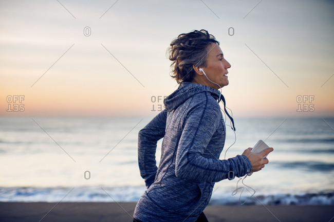 Middle age woman jogging on beach