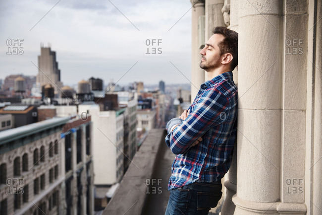 Man on office balcony resting