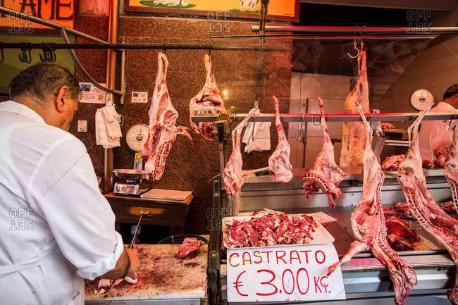 Butcher cutting meat at Catania market, Sicily, Italy