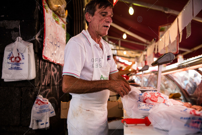 Catania, Sicily - July 25, 2015: Butcher packaging purchase in a plastic bag at Catania market, Sicily, Italy
