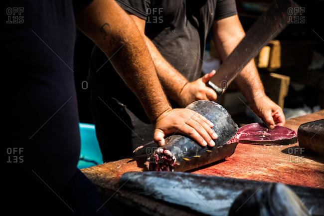 Fishmonger cutting tuna at La Pescheria, Catania, Sicily, Italy