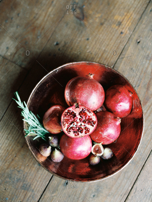 Copper bowl with pomegranates, figs and rosemary