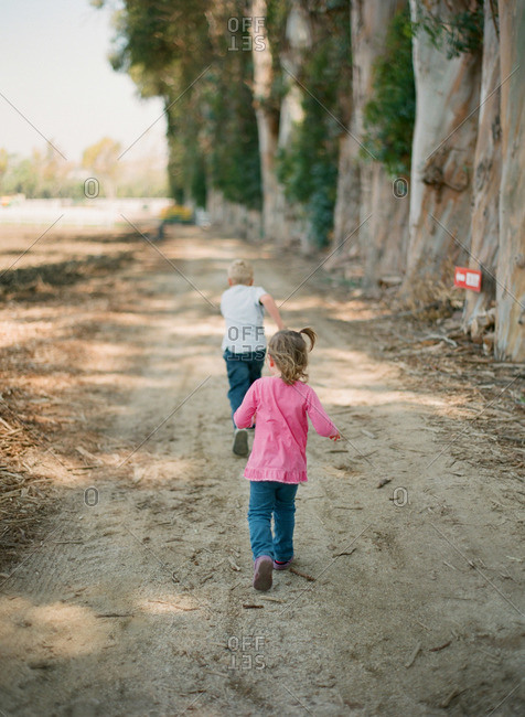 Children running along a dirt path lined with tall tree trunks