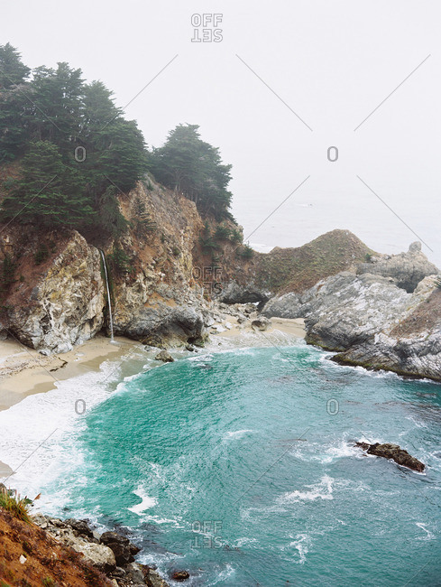 Blue waters and a beach in a rocky cove