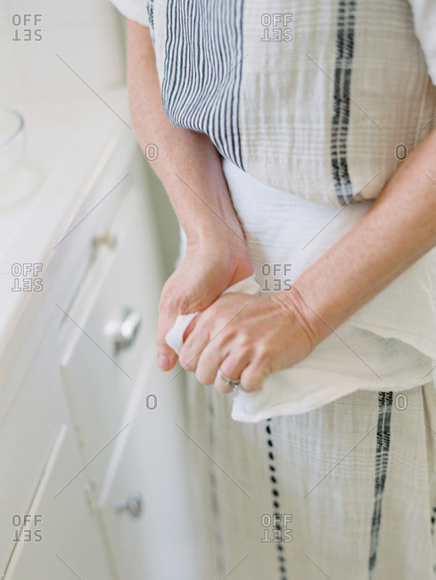 Woman wiping her hands on a cloth in a kitchen