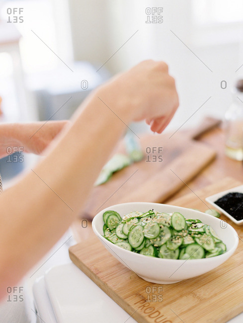 Woman sprinkling spices on top of sliced cucumbers