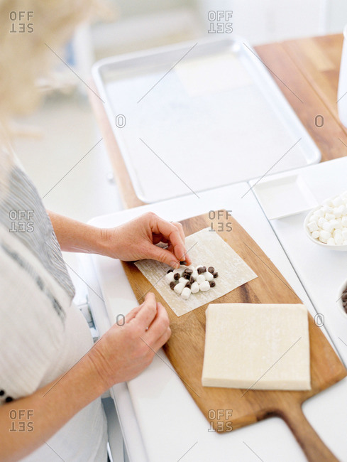 Woman putting chocolate chips and marshmallows in wonton wrappers