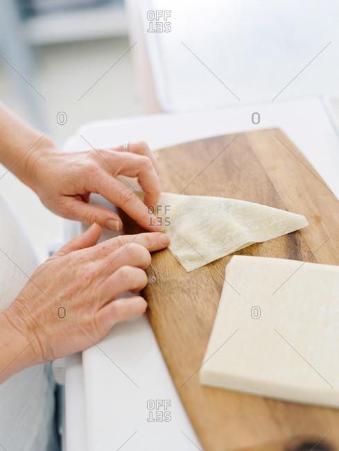 Hands of a woman closing a wonton wrapper dessert