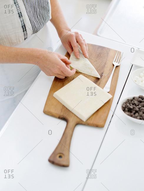 Woman folding a wonton wrapper dessert