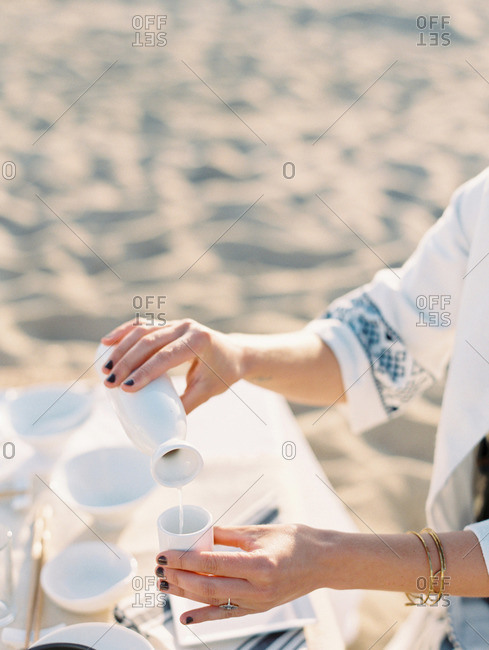 Woman pouring a beverage into a small cup at a beach picnic